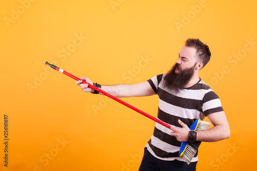 Fat young man picking up a broom as if it were a guitar - 256161697