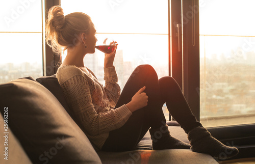 Obraz na plátne Woman sitting on the sofa, drinking red wine while looking out from the window