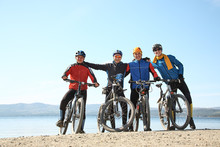 Group Of Cyclists On Shore Of A Mountain Lake. Team Outdoors. Mountain Bike