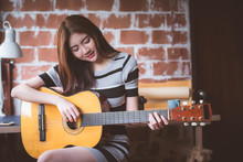 Young Beautiful Asian Woman Is Playing Acoustic Guitar At Her Working Room, Vintage Warm Tone