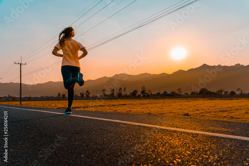 Asian woman enjoys running outside with beautiful summer evening in the countryside Fototapete