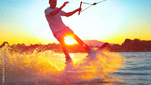 Vászonkép LENS FLARE, CLOSE UP: Young surfer wakeboarding and jumping 180 ollie at sunset