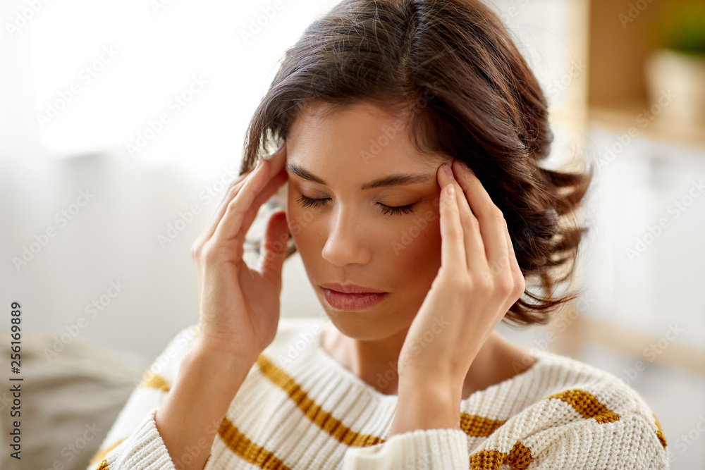Fototapeta people , health and stress concept - unhappy woman suffering from head ache at home