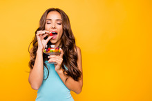Close Up Photo Beautiful Her She Wavy Lady Eyes Closed Hold Hands Arms Goblet Little Candy Sweets Get One Into Open Mouth Wear Blue Teal Green Everyday Short Dress Clothes Isolated Yellow Background
