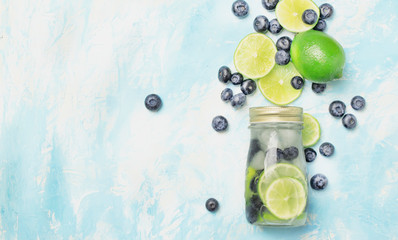 Summer cold drink with blueberry, lime and ice in glass bottle, top view