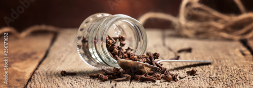Fototapeta Cloves sticks in silver spoon and glass jar, old wooden table background, banner, selective focus obraz