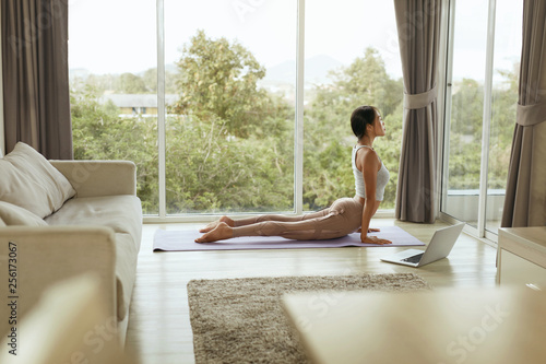 Fotobehang Ontspanning Girl doing yoga training, stretching body at home with computer