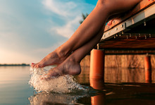 Woman Legs As She Sitting On Wooden Dock By The Lake.