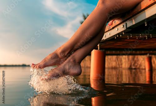 Fotografie, Obraz Woman legs as she sitting on wooden dock by the lake.