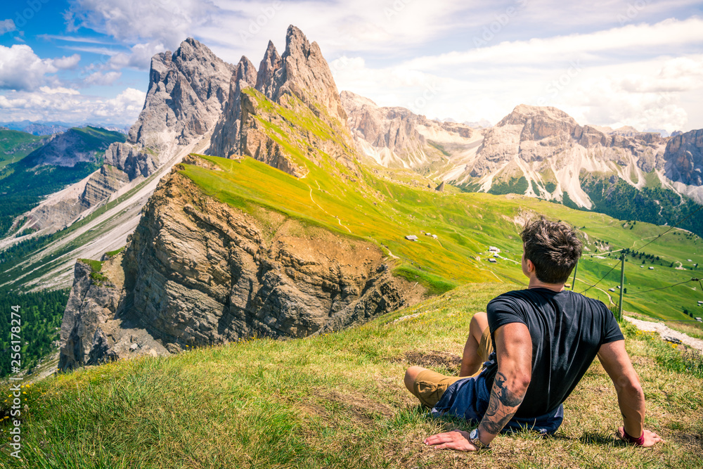 Fototapety, obrazy: beautiful young muscular man sitting on the grass enjoying the beautiful dolomites mountains landscape. seceda, 2500m over the odle group mountains