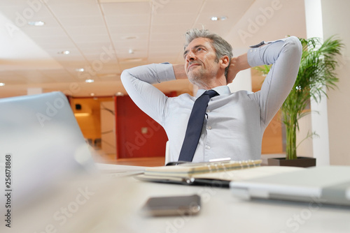 Obraz Mature businessman relaxing at desk in office - fototapety do salonu