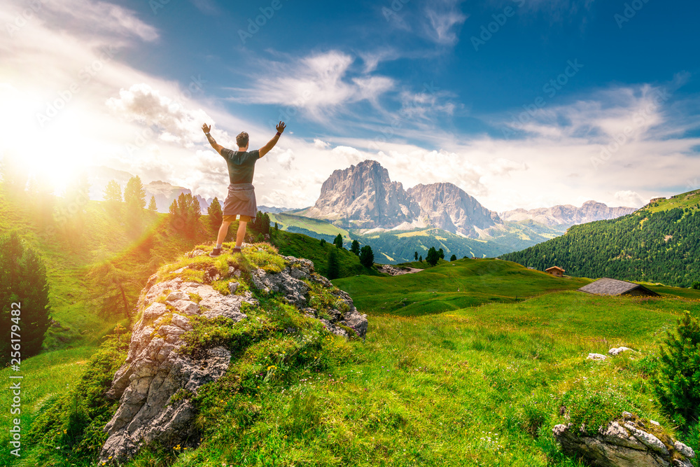 Fototapety, obrazy: young beautiful hiker men with raised hands standing on the top of a rock enjoying the mountain view of the dolomites in val gardena, south tyrol