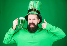 Thumbs Up If You Have A Drink. Bearded Man Toasting To Saint Patricks Day. Irish Man With Beard Drinking Green Beer. Hipster In Leprechaun Hat Holding Beer Mug. Celebrating Saint Patricks Day In Bar