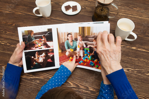 Obraz Hand senior woman and child holding a family photo album against the background of the a wooden table. - fototapety do salonu