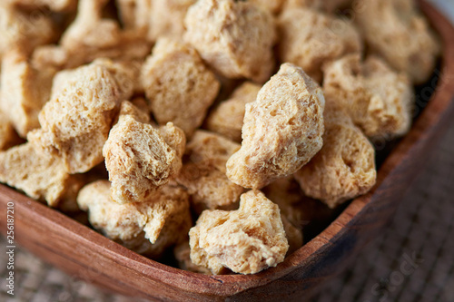 Raw soya chunks, soy meat for vegans in wooden bowl