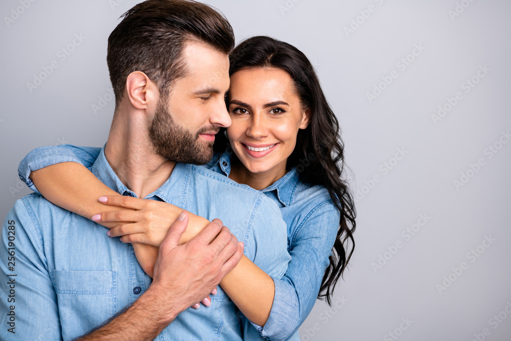 Fototapeta Love affair. Portrait of charming couple of millennial cheerful positive placing hands around chest wavy curly hair wearing blue denim shirts isolated on grey background