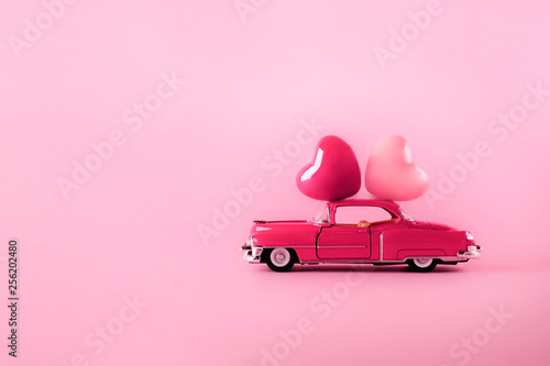 Fotografía Pink retro toy car delivering hearts on a pink background