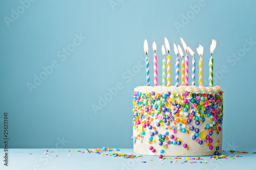 Birthday cake decorated with colorful sprinkles and ten candles