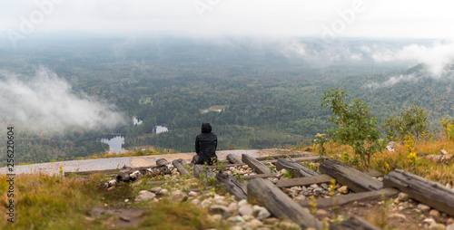 Photo a woman looks over a foggy drizzly landscape in the Adirondacks