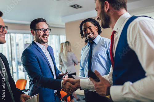 Cuadros en Lienzo Happy businessmen handshaking after negotiation in office