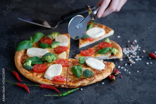 Fotografie, Obraz  Sliced pizza with Mozzarella cheese, tomatoes, broccoli, Spices and fresh basil on black stone background