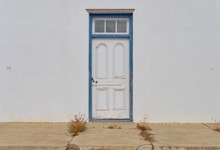 Minimalist Capture Of A Single Rural Door On A White Textured Wall.  Door Has Blue Frame In A State Of Needing Repairs. Front Concrete Porch With Weeds