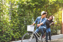 Happy Couple Riding Bicycle Together In Romantic View Park Background. Valentine's Day And Wedding Honeymoon Concept. People And Lifestyles Concept.