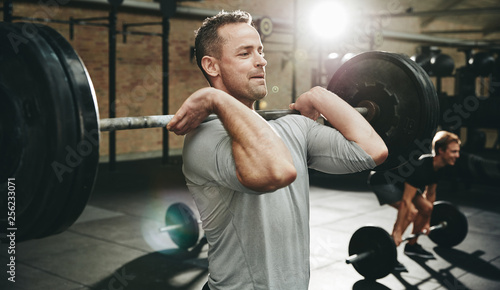 Fotografie, Obraz  Fit man doing weight training at the gym