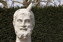 Close-up: Old Bust Of Horned Greek God Is On Left Side Of Nature Background Green Wall Outside. One Horn Is Missing. Copy Space Is On The Right.