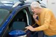 Senior man buying a new car at the dealership