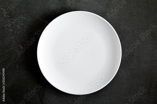 Empty white plate on black background table. Flat lay, top view, copy space
