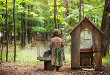 Rear View Of Girl Standing By Rabbit Hutch In Forest