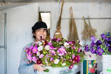 Woman Carrying Basket Of Flowers In Workshop