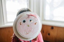 Girl Holding Plate Mask At Home