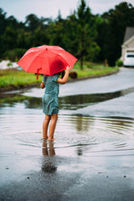Rear View Of Girl Holding Umbrella While Standing On Road