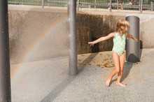Playful Girl Enjoying Summer Vacation In Fountain On Sunny Day