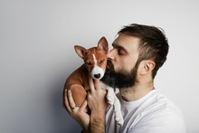 Happy Bearded Young Man Looking At Amazing Cute Basenji Puppy Sniffing His Nose