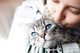 Woman at home holding her lovely fluffy cat. Gray tabby cute kitten with blue eyes. Pets, friendship, trust, love, and lifestyle concept. Friend of human. Animal lover.
