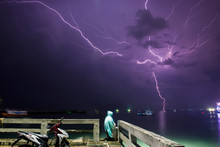 Person Sitting On Pier By Sea Against Lightning In Sky
