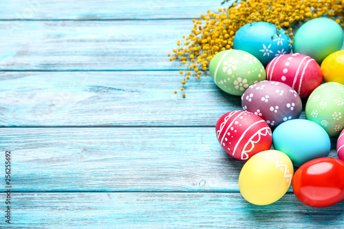 Fotografia  Colorful easter eggs with yellow flowers on blue wooden table