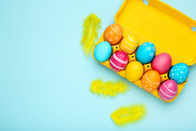 Colorful Easter Eggs In Carton Box With Yellow Feathers On Blue Background