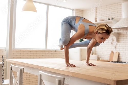 Fotografija  Concentrated young woman completing extremely hard pose on kitchen table