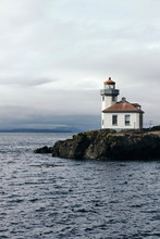 View Of Lighthouse At Seashore Against Cloudy Sky