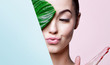 Leinwandbild Motiv Portrait of young beautiful woman with healthy glow perfect smooth skin holds green tropical leaf, look into the hole of colored paper. Model with natural nude make up. Fashion, beauty, skincare.