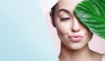 Portret mlade lijepe žene sa zdravim sjajem, savršena glatka koža drži zeleni tropski list, pogledajte u rupu obojenog papira. Model s prirodnim golišavim make upom. Moda, ljepota, njega kože.