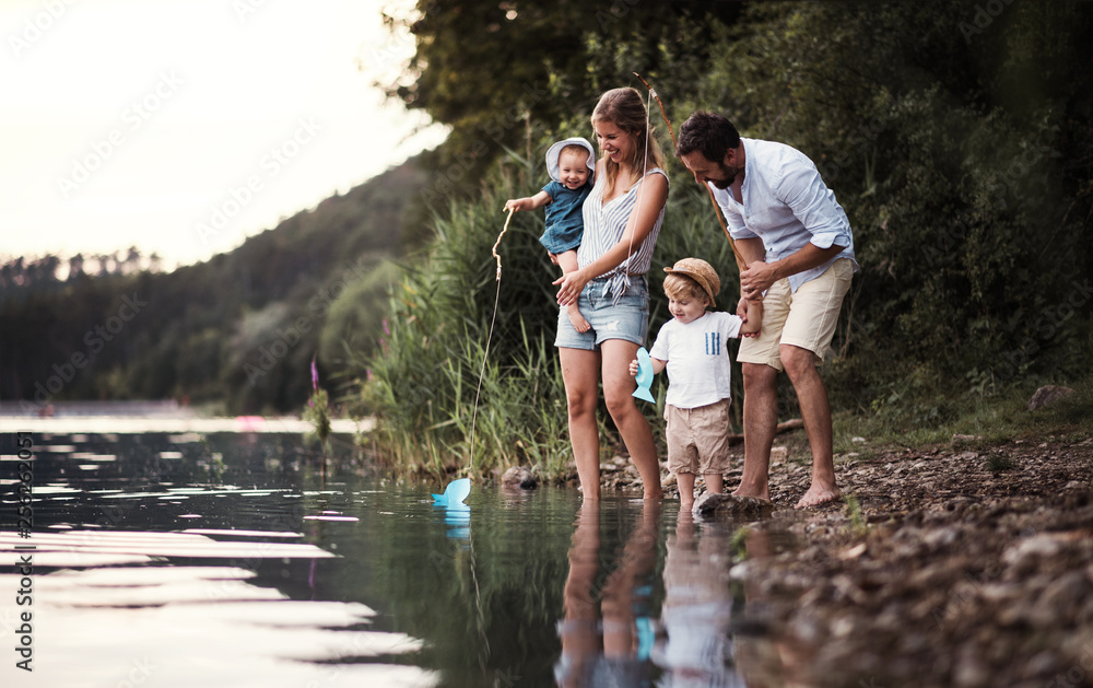 Fototapety, obrazy: A young family with two toddler children outdoors by the river in summer.