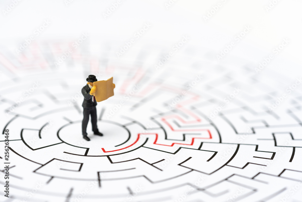 Fototapeta Miniature people, businessman in the labyrinth or maze figuring out the way out. Business concept, finding solution, strategic, and business opportunity.