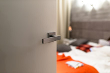 Ajar Door To A Modern Bedroom With A Light, Visible Blurred Bed, Bedding And Orange Pillows.