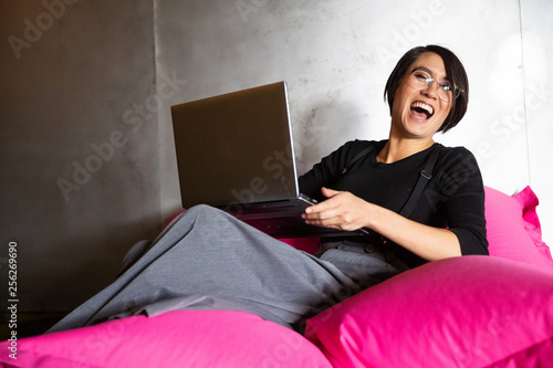 Pretty Asian woman working on laptop while sitting on beanbag chair in office Wallpaper Mural