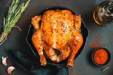 Pieczony cały kurczak z przyprawami na patelni z czarnego żelaza na stole.